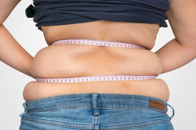 overweight woman measuring fat on midsection